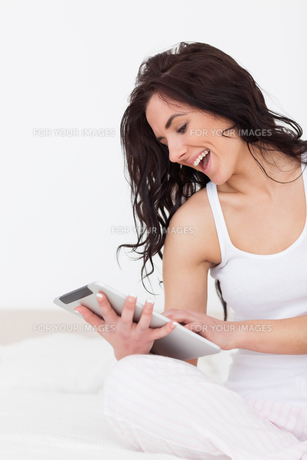 Cheerful woman holding her tablet pc while sittingの素材 [FYI00485138]
