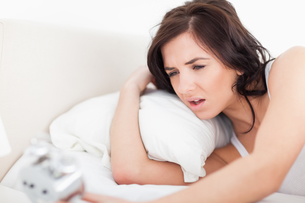 Brunette woman waking up while looking at her alarm clockの写真素材 [FYI00485140]