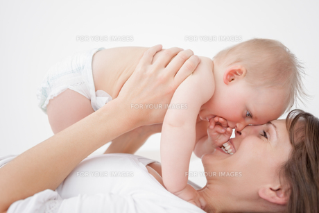 Happy mother holding her daughter while lyingの写真素材 [FYI00485156]