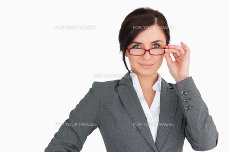 Seductive businesswoman holding her glassesの素材 [FYI00485165]