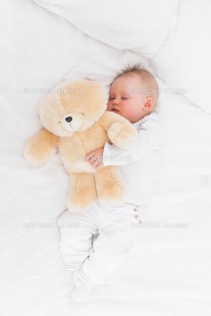 Baby sleeping while holding a teddy bearの写真素材 [FYI00485166]