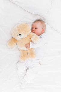 Baby sleeping while holding a teddy bearの写真素材 [FYI00485166]