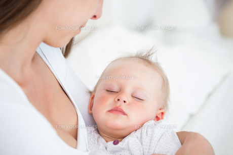 Baby falling asleep in the arms of her motherの素材 [FYI00485169]