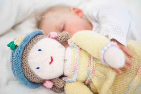 Baby sleeping while holding a plush dollの素材 [FYI00485171]