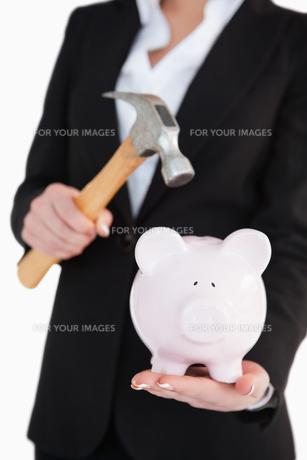 Businesswoman holding a piggy-bank and a hammerの写真素材 [FYI00485172]
