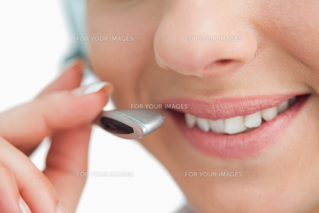Close-up on a smiling businesswoman mouth speaking in headsetの写真素材 [FYI00485183]