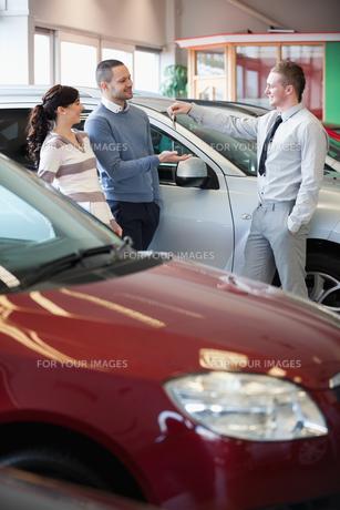 Smiling salesman giving keys to a happy coupleの写真素材 [FYI00485185]
