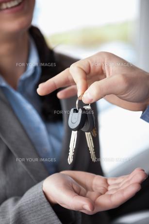 Woman smiling while receiving keysの素材 [FYI00485187]