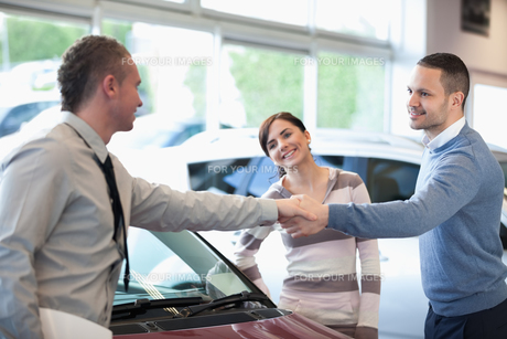 Car dealer shaking hand with a smiling manの写真素材 [FYI00485188]