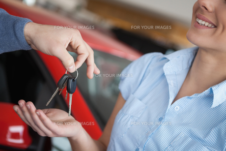 Smiling woman receiving keys from somebodyの写真素材 [FYI00485191]