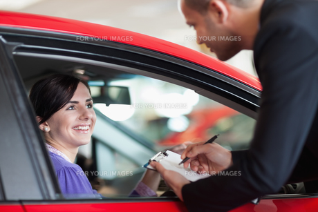 Woman in a car talking with a salesmanの素材 [FYI00485193]