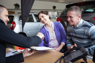 Couple chatting with a car salesmanの写真素材 [FYI00485194]