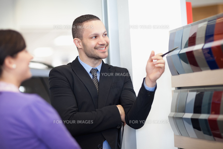 Smiling salesman pointing at a color paletteの素材 [FYI00485198]
