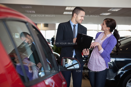 Salesman talking to a smiling woman next to a carの素材 [FYI00485199]