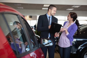 Salesman talking to a smiling woman next to a carの写真素材 [FYI00485199]
