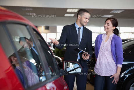 Salesman showing a car to a womanの素材 [FYI00485200]