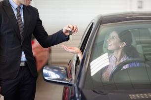 Smiling woman in a car taking keysの写真素材 [FYI00485205]