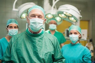 Smiling surgeon posing with a teamの写真素材 [FYI00485217]