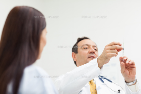 Doctor checking an injection for a patientの写真素材 [FYI00485231]