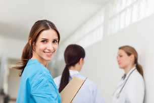 Smiling nurse  while standing in a hallway with a patient and a doctorの写真素材 [FYI00485239]