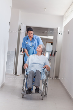 Nurse pushing a patient in a wheelchairの写真素材 [FYI00485242]