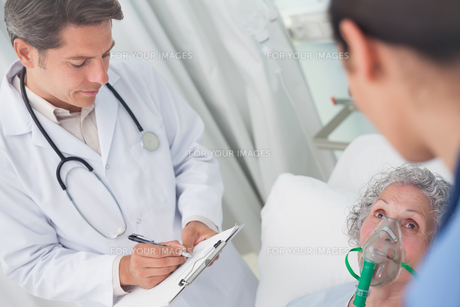 Doctor writing on a clipboard with a penの写真素材 [FYI00485243]