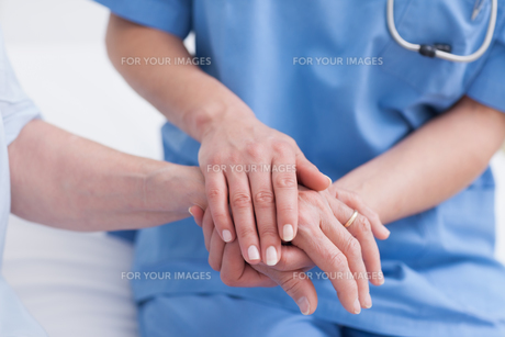 Close up of a nurse touching hand of a patientの素材 [FYI00485250]