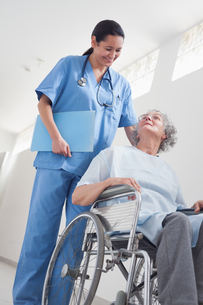 Elderly patient in a wheelchair next to a nurseの素材 [FYI00485252]