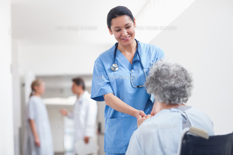Nurse standing next to a patient while holding her handsの素材 [FYI00485255]