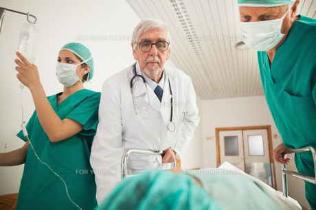 Doctor and surgeon looking at a patientの写真素材 [FYI00485268]
