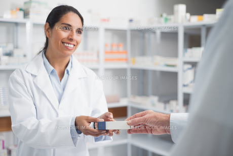 Smiling pharmacist giving a box to a doctorの素材 [FYI00485269]