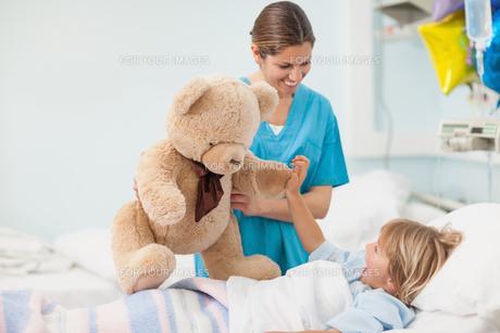Nurse showing a teddy bear to a childの写真素材 [FYI00485277]