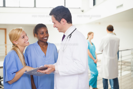 Doctor showing a clipboard to nursesの写真素材 [FYI00485304]