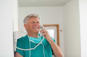 Surgeon smiling while holding a phoneの写真素材 [FYI00485309]