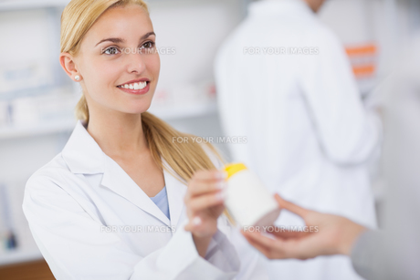 Blonde pharmacist giving a drug boxの写真素材 [FYI00485310]