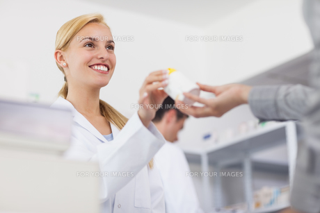 Pharmacist giving a drug box to a patientの素材 [FYI00485311]