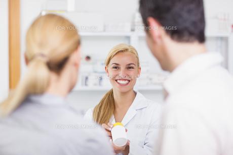 Blonde pharmacist holding a drug boxの写真素材 [FYI00485312]