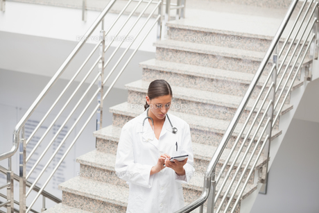 Doctor using a tablet computer on stairsの素材 [FYI00485318]
