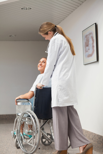 Patient sitting on a wheelchair looking at a doctorの素材 [FYI00485321]