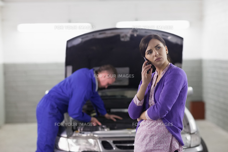 Client holding a mobile phone next to a carの写真素材 [FYI00485332]