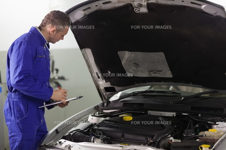 Mechanic holding a clipboard while looking at a car engineの写真素材 [FYI00485333]