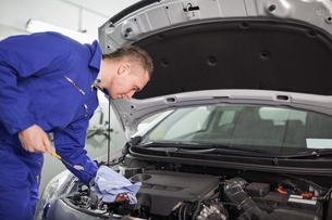 Mechanic looking at a dipstick while holding itの素材 [FYI00485334]