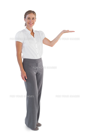 Smiling businesswoman presenting something with her handの写真素材 [FYI00485354]