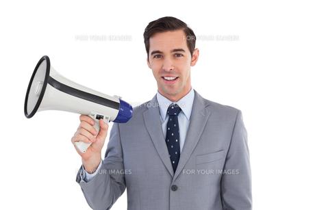 Smiling businessman holding a megaphoneの写真素材 [FYI00485356]