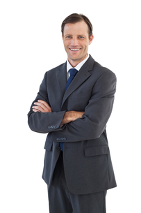 Charismatic smiling businessman standing with arms crossedの写真素材 [FYI00485358]