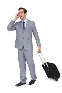 Smiling young businessman with his luggage while phoningの写真素材 [FYI00485360]