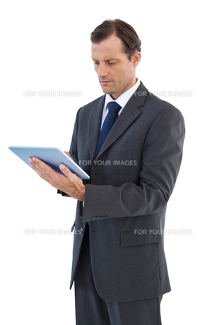 Charismatic businessman holding a tablet pcの写真素材 [FYI00485364]