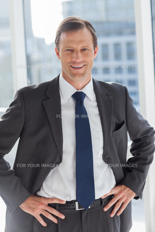 Smiling businessman with his hands on hipsの写真素材 [FYI00485367]