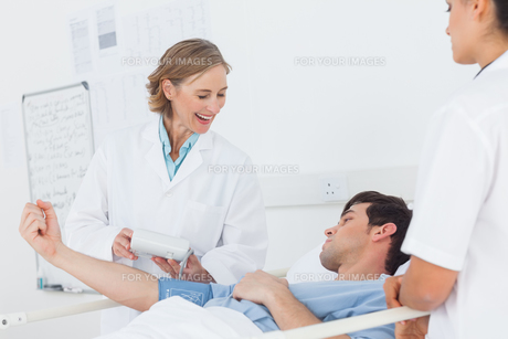 Smiling doctor measuring blood pressure of a patientの写真素材 [FYI00485390]