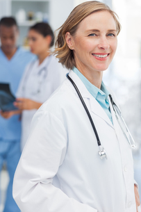 Smiling woman doctor in front of medical teamの素材 [FYI00485393]